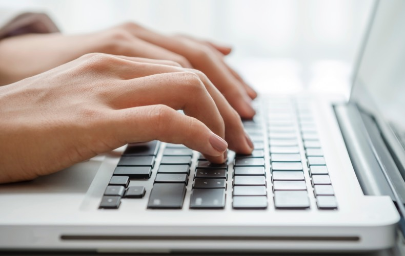 Close-up of hand typing on laptop keyboard